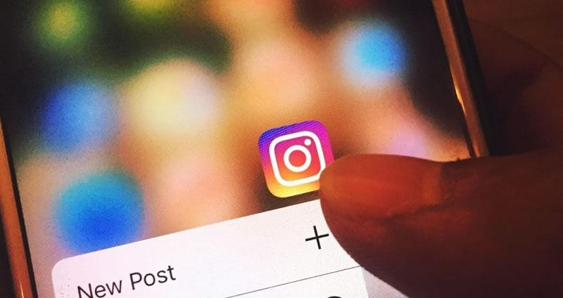 Pessoa usando o smartphone para acessar o Instagram do seu consultório odontológico.